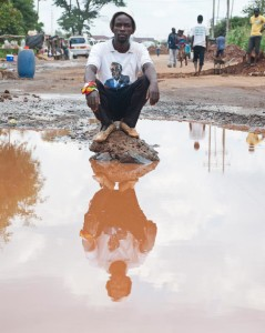 From a series titled 'MABASA' - Tanaka, a volunteer pothole repairman at the section of road he maintains in Budiriro, in the absence of formal employement, he and two friends earn a meagre living by charging a toll for filling in potholes